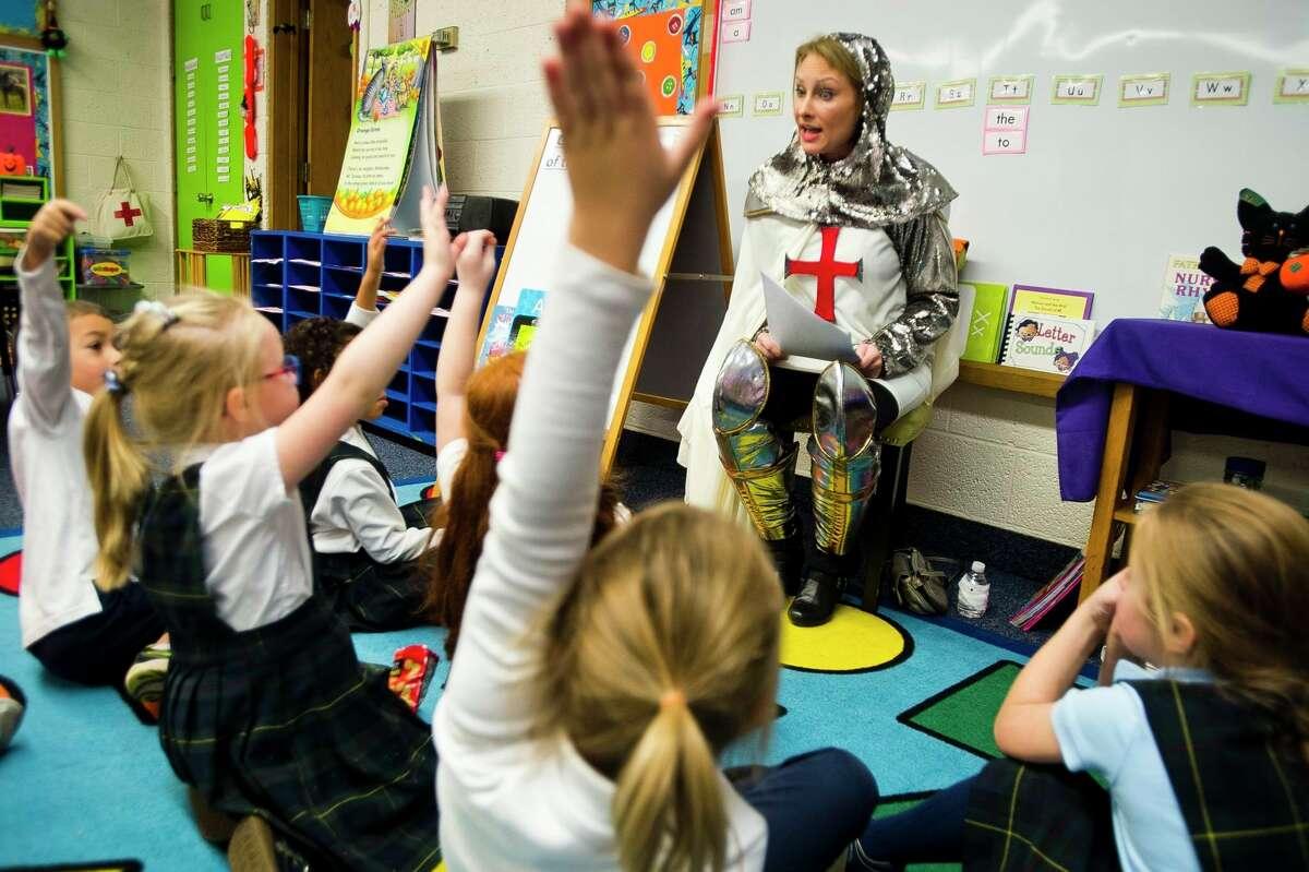 Midland resident Sarah Selaty, dressed as St. Joan of Arc, speaks to a group of children at Blessed Sacrament School in celebration of All Saints' Day on Thursday, Nov. 1, 2018. (Katy Kildee/kkildee@mdn.net)
