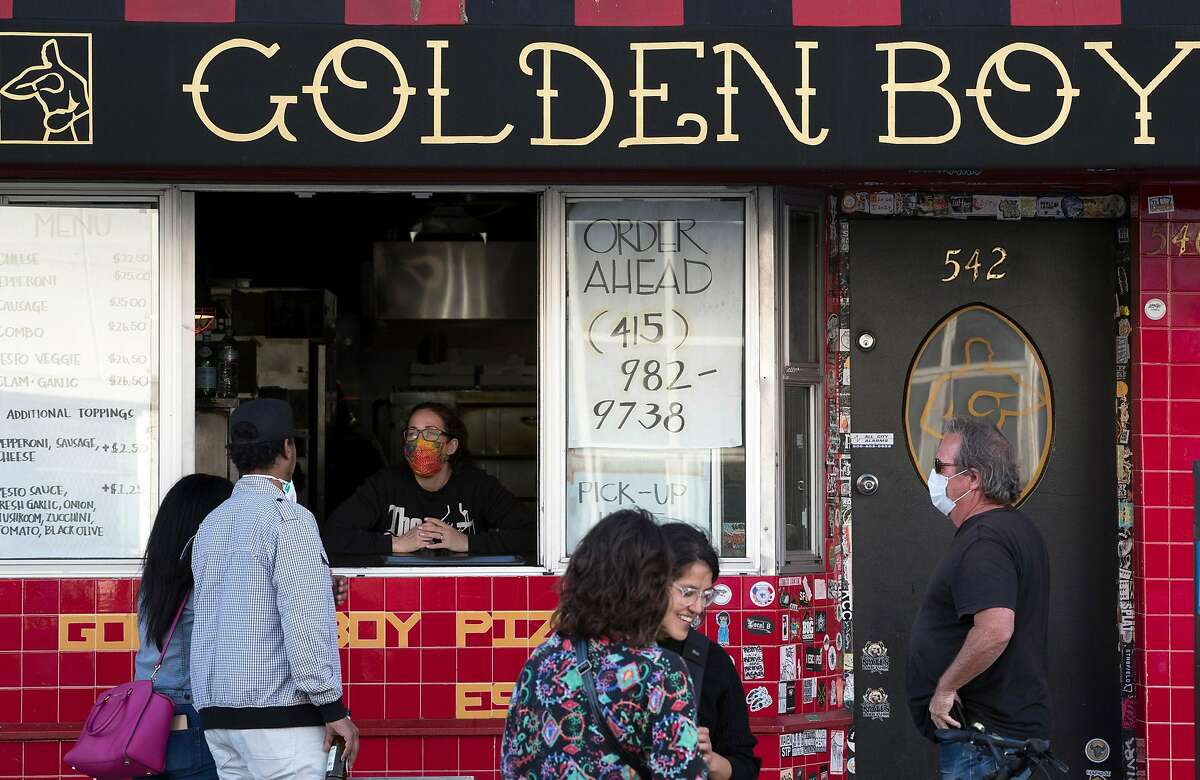 Golden Boy Pizza has sidewalk pick up in San Francisco, Calif., on Tuesday, June 16, 2020. The transitional post-shelter in place phase of landscape of San Francisco dining establishments is starting. Eateries try to stir back into action, but with a burden of constraints of protecting their customers. Several places on Belden Place are coming back with spaced outdoor tables, and several places on Green Street between Grant and Columbus are testing the waters as well with new dining in the street.