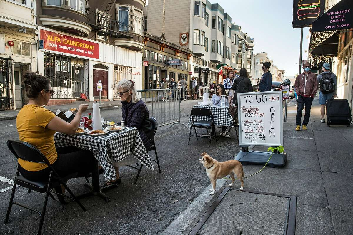 A makeshift outdoor dining area bounded by steel barricades in San Francisco.
