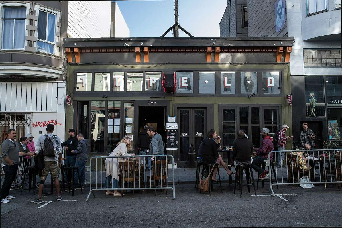 Guests gather at outdoor tables at Tupelo in San Francisco, Calif., on Tuesday, June 16, 2020. The transitional post-shelter in place phase of landscape of San Francisco dining establishments is starting. Eateries try to stir back into action, but with a burden of constraints of protecting their customers. Several places on Belden Place are coming back with spaced outdoor tables, and several places on Green Street between Grant and Columbus are testing the waters as well with new dining in the street.