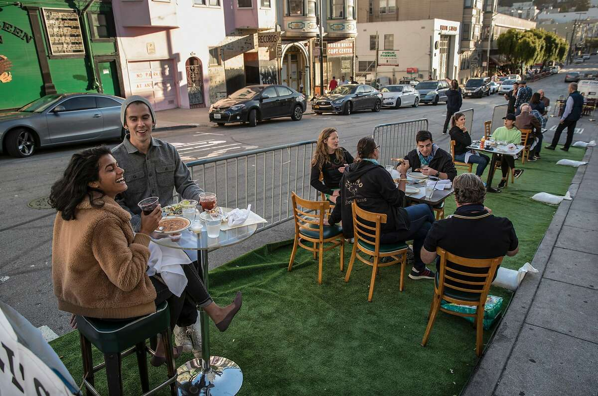 Diners at Sodini's Green Valley Restaurant at their outdoor tables on synthetic grass in San Francisco, Calif., on Tuesday, June 16, 2020. The transitional post-shelter in place phase of landscape of San Francisco dining establishments is starting. Eateries try to stir back into action, but with a burden of constraints of protecting their customers. Several places on Belden Place are coming back with spaced outdoor tables, and several places on Green Street between Grant and Columbus are testing the waters as well with new dining in the street.