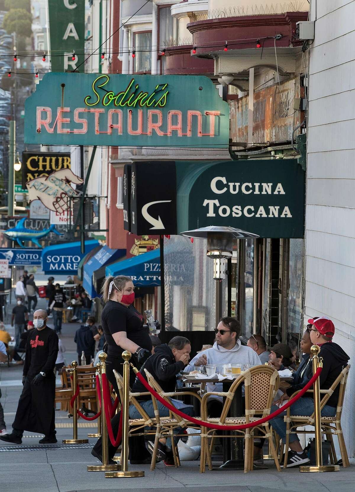 Diners at Sodini's Green Valley Restaurant are taken care of at their outdoor tables by waitstaff in San Francisco, Calif., on Tuesday, June 16, 2020. The transitional post-shelter in place phase of landscape of San Francisco dining establishments is starting. Eateries try to stir back into action, but with a burden of constraints of protecting their customers. Several places on Belden Place are coming back with spaced outdoor tables, and several places on Green Street between Grant and Columbus are testing the waters as well with new dining in the street.