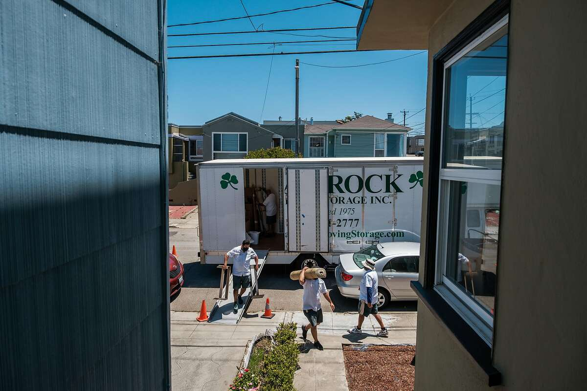 Movers help move a client's belongings into a house in San Francisco on June 17, 2020.