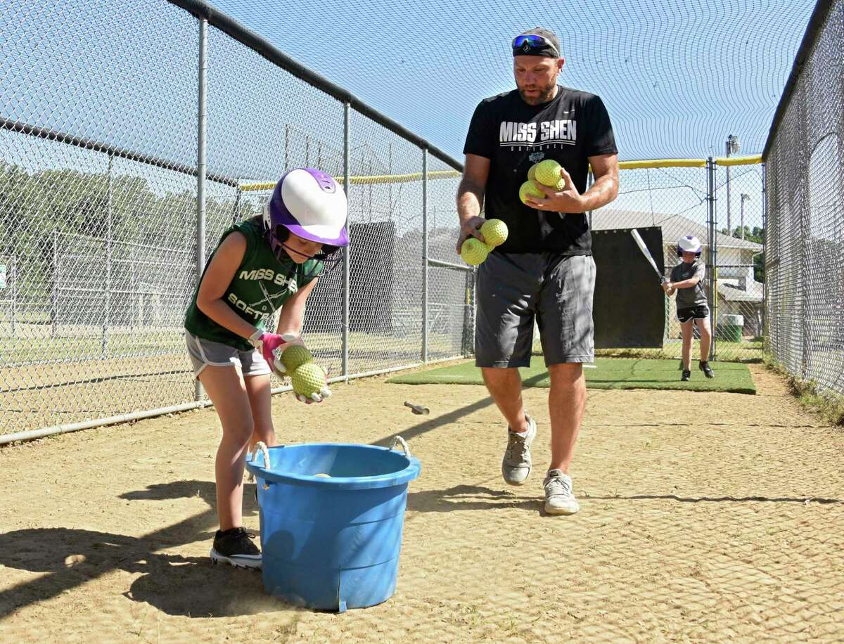 Amanda Milby, 10, and coach Rob Groelz gather softballs in the batting cage as the Miss Shen softball program holds batting practice for the 10-and-under travel team at Clifton Common on Wednesday, June 17, 2020 in Clifton Park, N.Y. Clare Hurst, 10, takes some practice swings at right. The players are getting closer to a resumption of their season in July. (Lori Van Buren/Times Union)