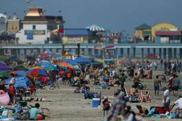 People enjoy the weather at the beach near the Seawall on Sunday, May 24, 2020, in Galveston, Texas. The city of Galveston will close its beaches to the public for the July 4th holiday weekend amid a spike in new coronavirus cases - and will consider closing certain access points for the rest of the summer, city officials said.