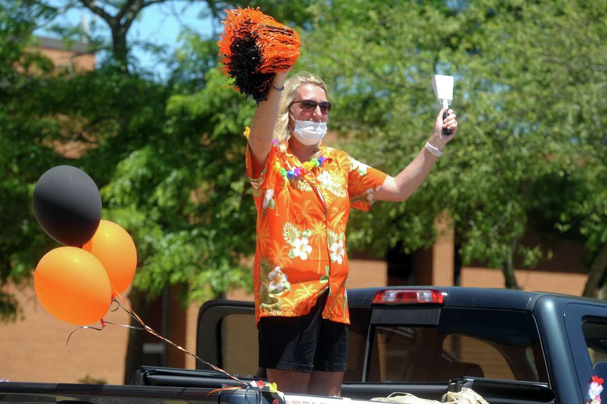 Interim Principal Kathy Riddle waves to passing students during the drive through parade for graduates at Shelton High School, in Shelton, Conn. June 17, 2020.
