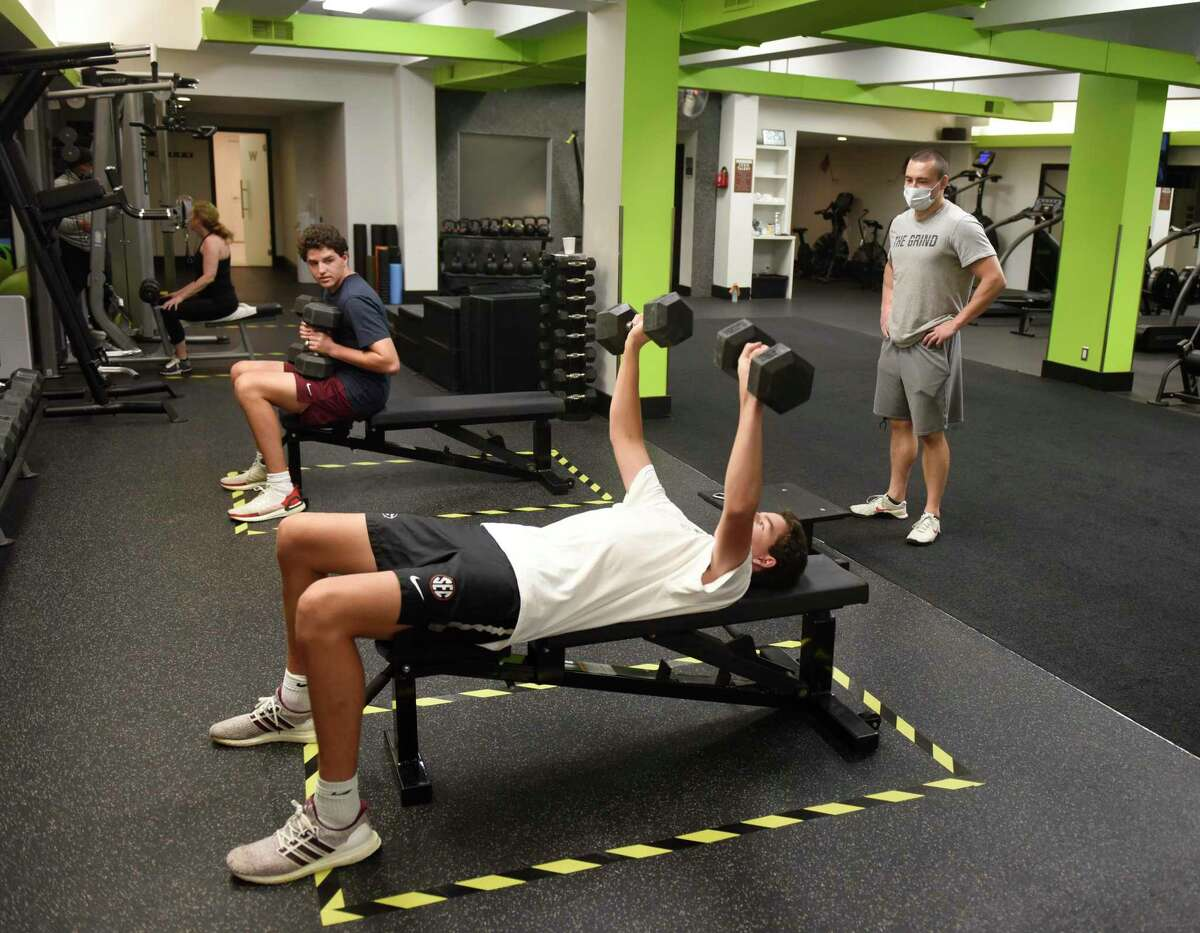 Greenwich brothers Alex Riddle, left, and Graham Riddle, both 17, work out with trainer Keith Kirwan at Mason Street Strength & Fitness.