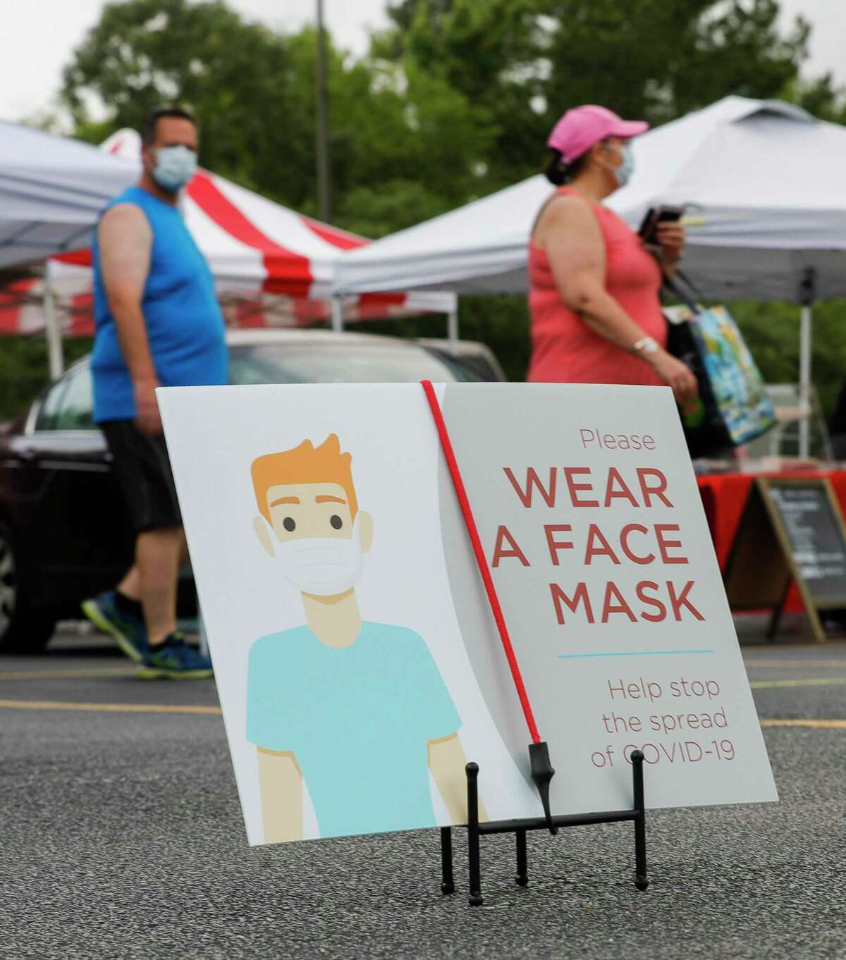 A sign reminds customers to wear a face mask while shopping at The Woodlands Farmers Market, Saturday, May 23, 2020, in The Woodlands.