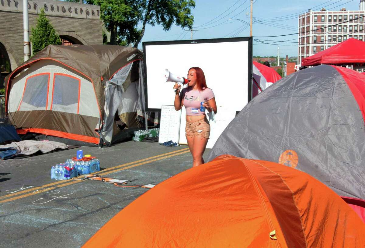 Protestor Mikaela Adams uses a bullhorn to make an announcement at the tent city in front of police headquarters on Congress Street in Bridgeport, Conn., on Wednesday June 17, 2020.