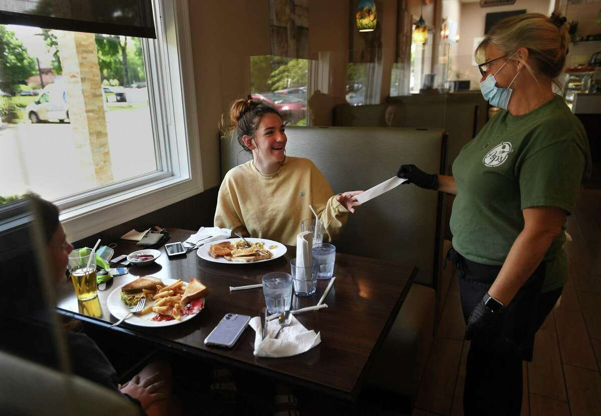 Taylor Firla, left, and Ava Candido, both of Milford, get the check from waitress Sharon Tomaso, of East Haven, during the first day of phase two reopening at Pop's Family Restaurant in Milford on June 17.