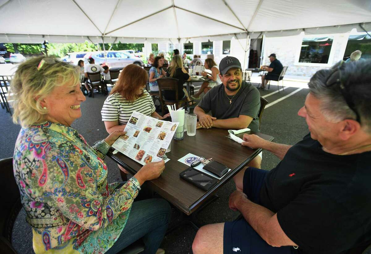 Jen, left, and Len Benigno, right, of Trumbull, dine with friends Lorraine and Sal Savoca, of Milford, during the first day of Phase II reopening at Pop's Family Restaurant in Milford, Conn. on Wednesday, June 17, 2020. The majority of patrons continue to dine beneath a large tent outside the restaurant.
