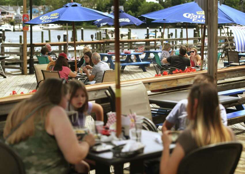 Customers dine outdoors on the first day of Phase II reopening at Joey C's Boathouse in Stratford, Conn. on Wednesday, June 17, 2020. The restaurant only plans on seating customers indoors during inclement weather.