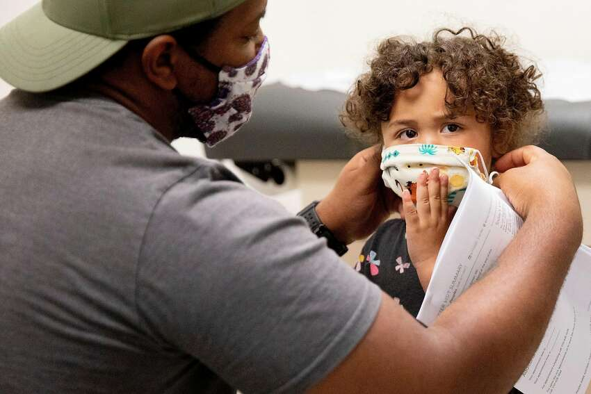 Marcus Peoples of Vallejo helps his daughter Scarlett, 3, put on her mask after being examined at UCSF Children's Hospital Claremont Clinic East in Oakland, Calif. Wednesday, June 17, 2020. As Bay Area hospitals cleared the way for the coronavirus surge that never came, preventative care and non-emergency surgeries ground to a halt. Now, hospitals are stressing it's safe to return for regular care that can't be done through telemedicine and even advertising to entice patients back, but some patients are still unable or choosing not to reschedule care