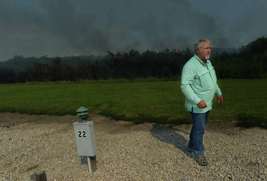 Richard Kibbe, a Louisiana resident who stays in an RV lot while working on a plant expansion project in Sabine Pass, watched as smoke and small crackling flames filled the brush behind the campground on Texas 87 just west of the high school Wednesday. Smoke from the large brush fire was visible for a couple miles, and formed a dense cloud of smoke over TX 87 west of the high school. Photo taken Wednesday, June 17, 2020 Kim Brent/The Enterprise Photo: Kim Brent / The Enterprise / BEN