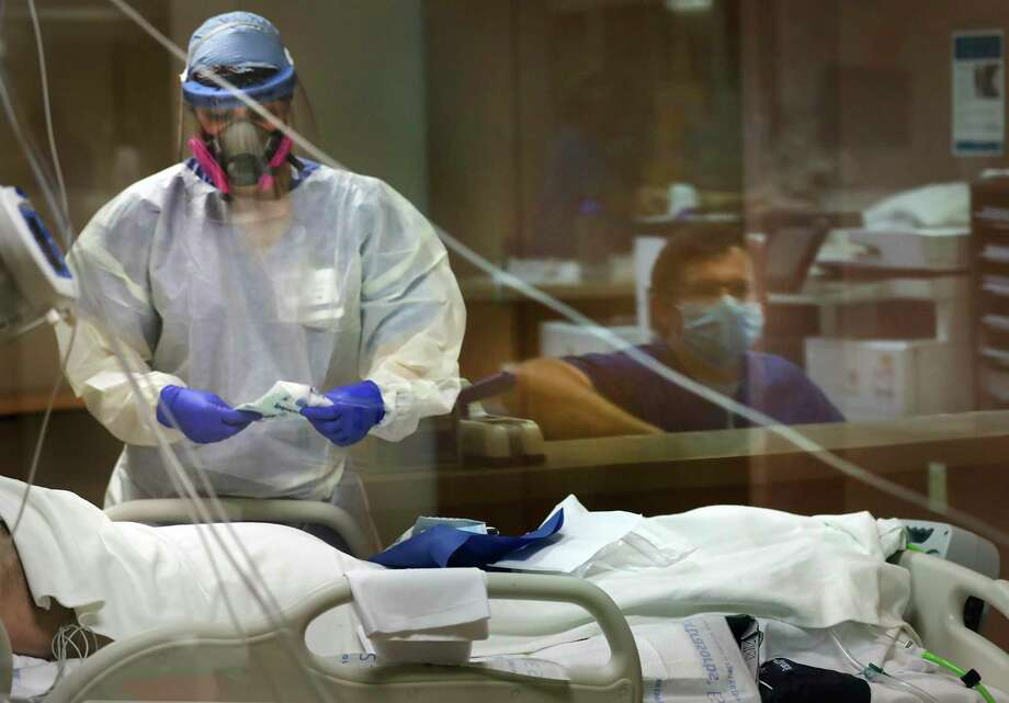 Evelyn Menking, left, tends to a patient in Northeast Baptist Hospital COVID-19 intensive care unit in this May 20, 2020., photo. Sam Beckett, right, the overnight charge nurse watches her. Bexar County officials reported that as of Wednesday evening, 241 COVID-19 patients were being treated in San Antonio-area hospitals, 91 of whom were in intensive care. Photo: Bob Owen /Staff Photographer / ©2020 San Antonio Express-News