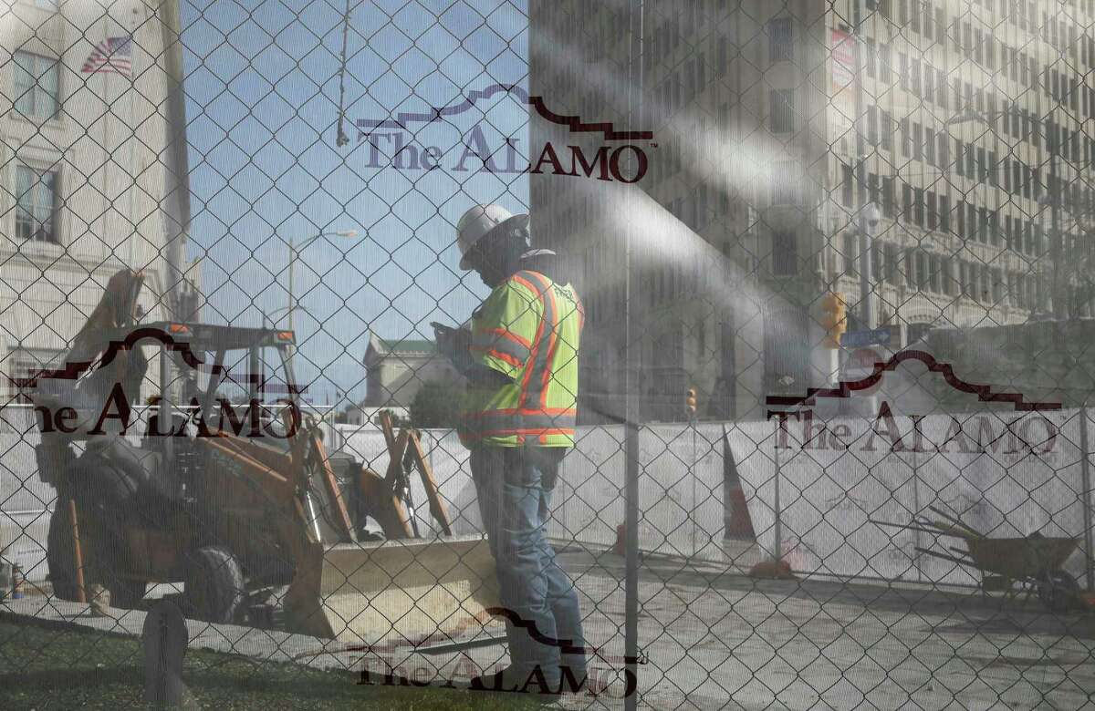 Construction workers are seen behind screens as work continues at Alamo Plaza, Monday, Dec. 16, 2019. On Friday, Alamo officials announced that three bodies found were found in Monks Burial Room and the Nave of the Alamo on Friday. According to a press release, the remains were of a teenager or young adult, an infant and an adult.