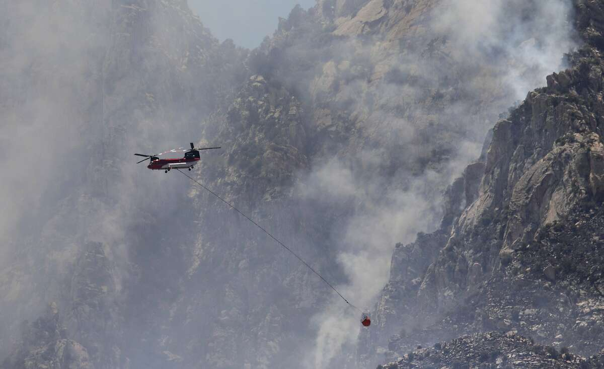 A Chinook helicopter flies along the past granite formations in a wildfire called the Bighorn Fire burning along Pusch Ridge of the Santa Catalina Mountains in Coronado National Forest, north of Tucson, Ariz., Sunday, June 7, 2020. The fire is at 1,000 acres and 0% contained, according to fire officials. (Rick Wiley/Arizona Daily Star via AP)