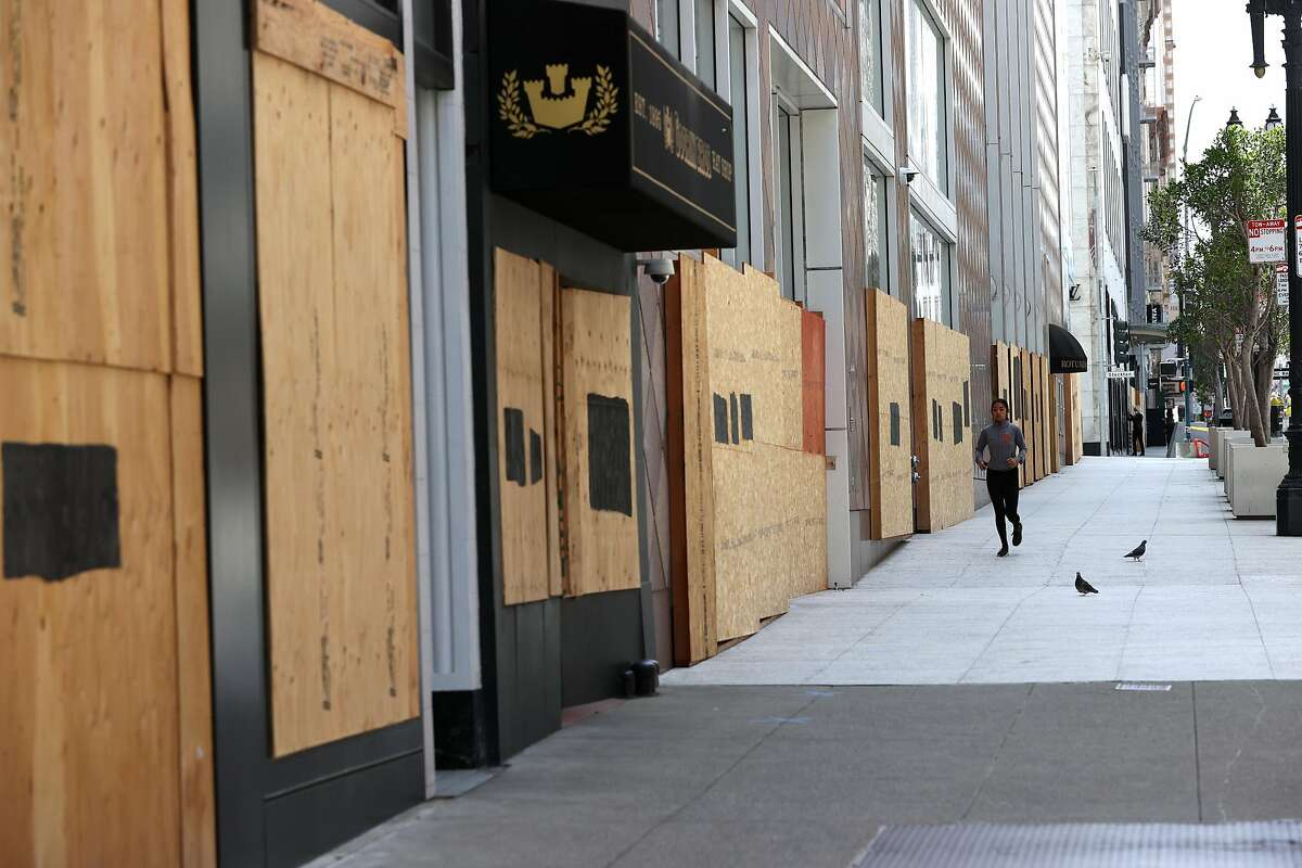 SAN FRANCISCO, CALIFORNIA - JUNE 11: A jogger runs by boarded up storefronts on June 11, 2020 in San Francisco, California. Economic worries due to the coronavirus COVID-19 pandemic continue as an additional 1.5 million people filed for first-time unemployment benefits in the past week. The Dow Jones Industrial average plunged over 1,800 points on the news. (Photo by Justin Sullivan/Getty Images)