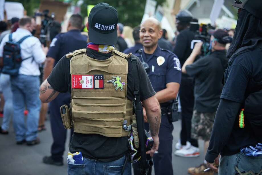 A member of the far-right militia, Boogaloo Bois, walks next to protestors demonstrating outside Charlotte Mecklenburg Police Department Metro Division 2 just outside of downtown Charlotte, North Carolina, on May 29, 2020. - The protest was sparked by protests in Minneapolis, over the death of George Floyd, a black man who died after a white policeman kneeled on his neck for several minutes. In Charlotte, CMPD Metro Division 2 was home to CMPD officer, Wende Kerl, who shot and killed Danquirs Franklin outside of a Burger King on March 25, 2019. CMPD found that officer Kerl operated in the constraints of the law but later a citizen review board would find that the officers actions were not justified. No charges were ever brought. Photo: (Photo By Logan Cyrus / AFP) (Photo By LOGAN CYRUS/AFP Via Getty Images)