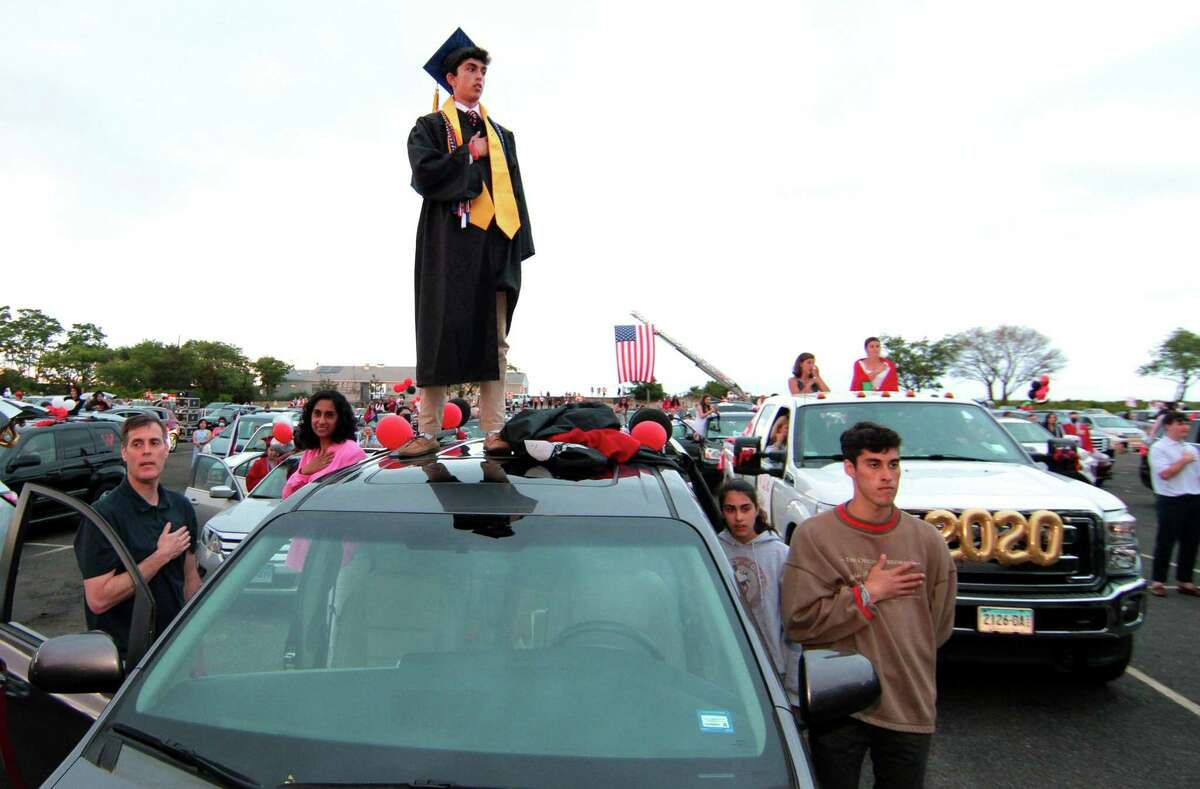 Graduate Brendan McMahon stands on the roof of the family vechicle as the Pledge of Allegiance is recited during Fairfield Warde's High School's Commencement Exercises at Jennings Beach in Fairfield, Conn., on Wednesday June 17, 2020.