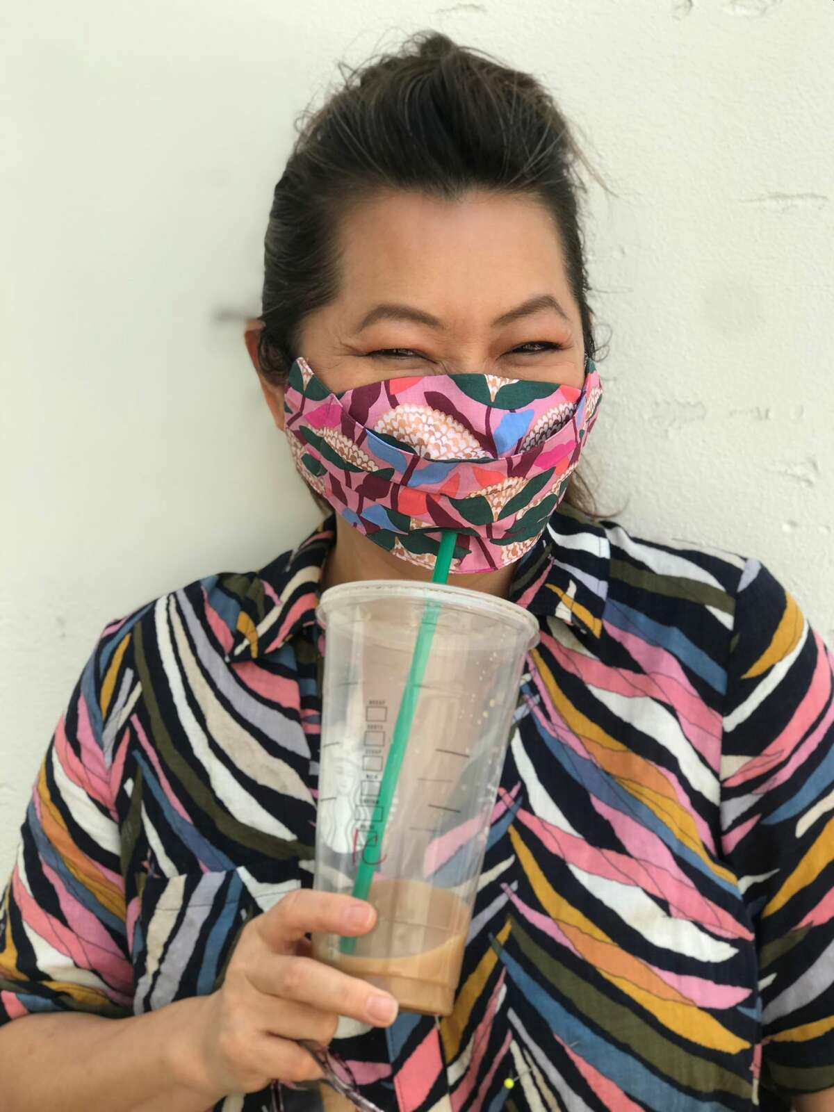 Project Runway winner and Houston fashion designer Chloe Dao wears her Safely Sip in Style mask, $25, which allow users to sip drinks through a straw without removing the mask.