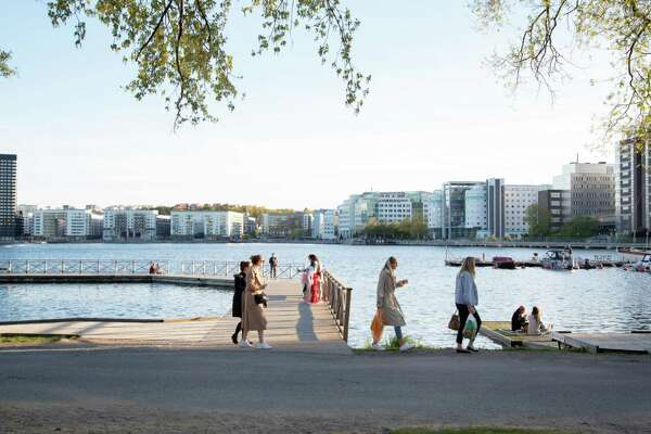 A group of people socialize on a jetty on the water's edge at Tantolunden in Stockholm, Sweden, on May 22, 2020.