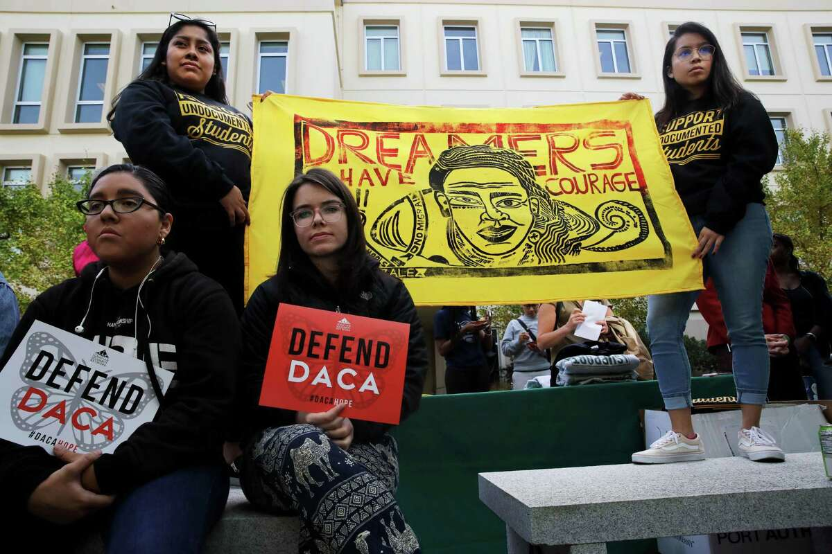 """Kiana Martinez, left, and Mariah O'Grady, hold """"Defend DACA"""" signs while Gladys Perez, left, of the Office of Diversity Engagement and Community Outreach at the University of San Francisco, and Diana Elizabeth Garcia Rodriguez, left, a graduate student, hold a """"Dreamers Have Courage"""" banner at USF protest in November 2019."""