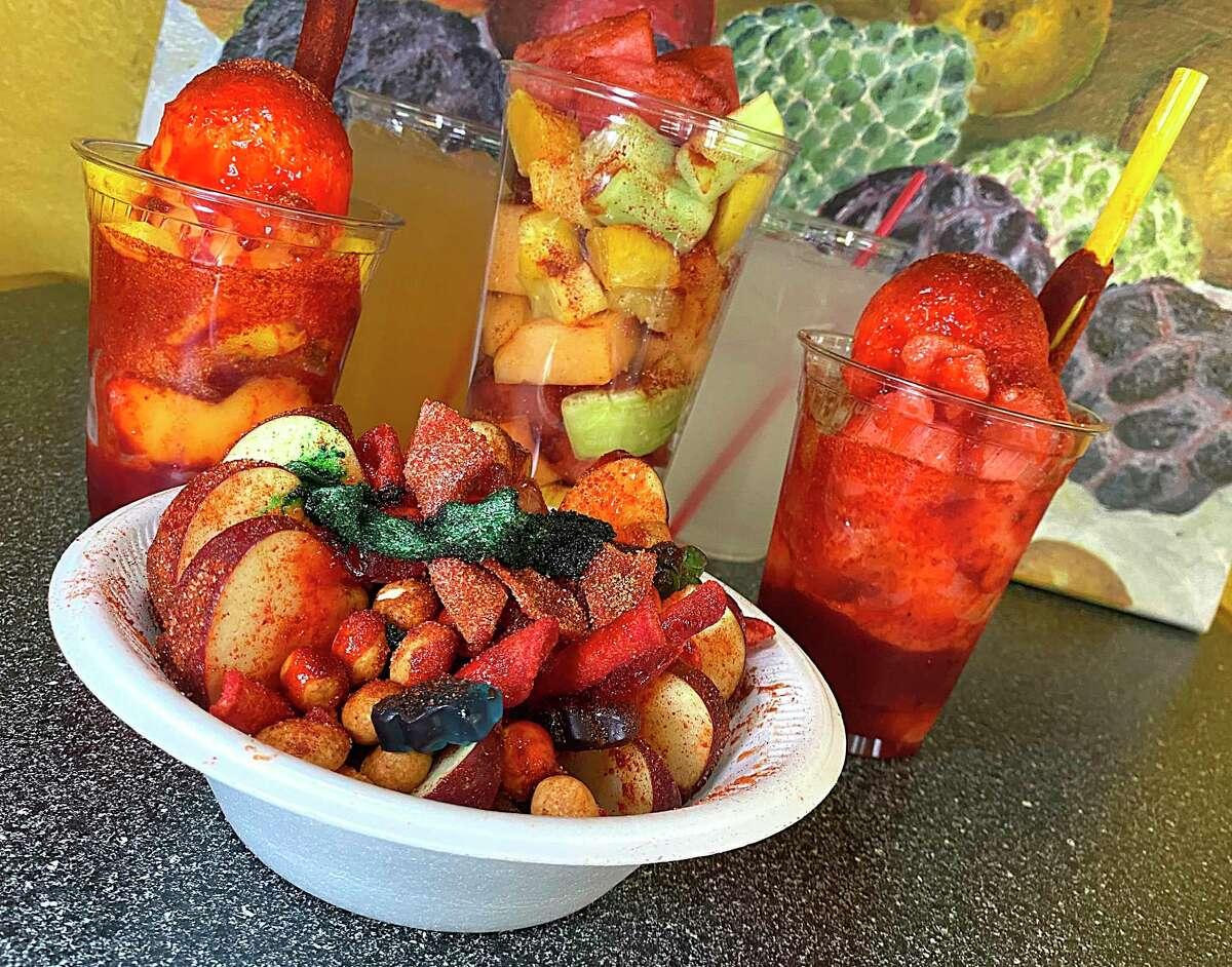 The fruit and snack menu at La Chiquita Frutería includes, clockwise from front, manzana loca, a mangonada, a cantaloupe agua fresca, a mixed fruit cup, lemonade and a sandianada.