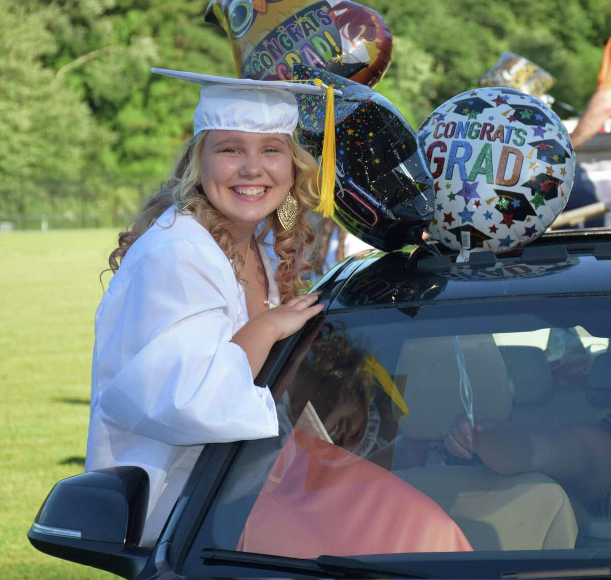 Sherman School held its eighth-grade graduation ceremony Saturday at Veterans Field. Students and their families arrived in a vehicle and parked in designated spots in the the field, where a ceremony was held adhering to social distancing guidelines. The majority of the cars were decorated. Above, Tijana Kanacki proudly awaits the start of the ceremony, joining fellow graduates by taking a creative seat in a vehicle. For more photographs, see Page S9.
