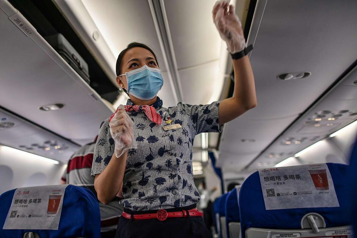A flight attendant wearing a facemask walks in a plane's alley of a flight to Shanghai at Tianhe Airport in Wuhan, in Chinas central Hubei province on May 29, 2020 The conclusion? Metal boxes filled with recirculated air travelling at 500 miles per hour, 38,000 feet above the ground are pretty good places to catch a virus, despite air filtration: