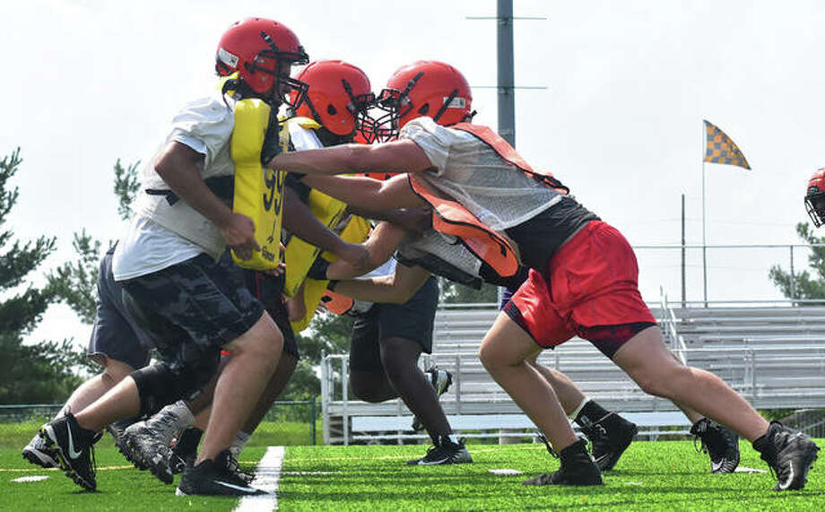 Members of the Edwardsville football team run through a drill during a practice last summer. This drill, along with others, can return by the end of the month if the latest proposal by the IHSA is accepted by the Illinois Department of Health. Photo: Matt Kamp|The Intelligencer