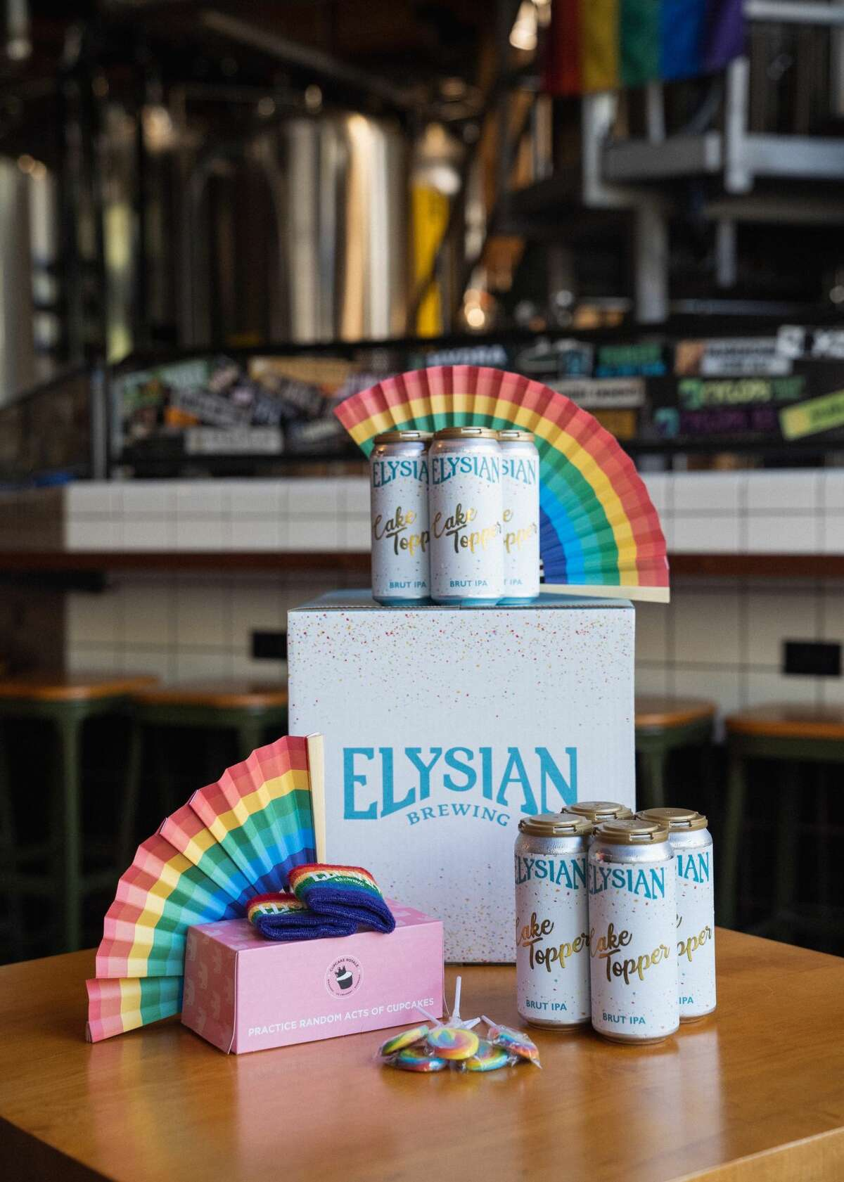 Cheers to celebrating love and equality... Elysian Brewing has created a pride box to help celebrate Seattle Pride virtually this year, filled with cupcakes, pride swag, and of course, beer. On June 4th, 2018, the Supreme Court ruled in favor of a cake shop owner who chose not to bake a wedding cake for a same-sex couple. One year after the Court decision, we chose to celebrate marriage equality by hosting a wedding in our Elysian Capitol Hill location. Cake Topper was brewed and released in honor of that special day. Elysian took the foundation of a Brut IPA and layered it with pink guava, vanilla, and lactose to emulate the flavors of a fruity, champagne-infused wedding cake. Inside their $25 pride boxes, enjoy eight Cake Topper 16oz cans, a 2-pack of