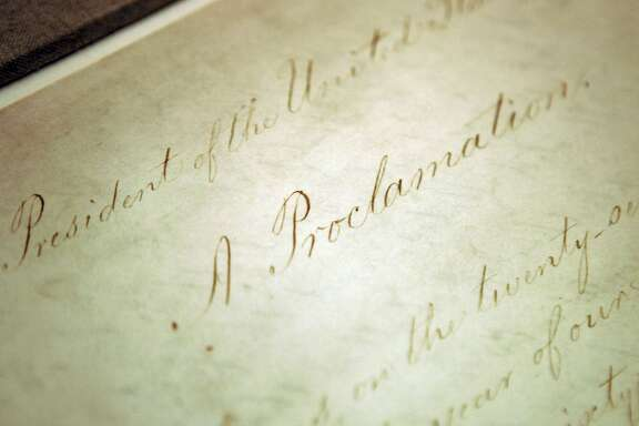 FILE - This Feb. 18, 2005, file photo shows the original Emancipation Proclamation on display in the Rotunda of the National Archives in Washington. President Abraham Lincoln first issued the Emancipation Proclamation declaring all slaves free in Confederate territory on Sept. 22, 1862. Juneteenth, the oldest holiday that commemorates the ending of slavery in the United States, originated 155 years ago.   Celebrations have typically included parades, barbecues, concerts and readings of the Emancipation Proclamation. (AP Photo/Evan Vucci, File)