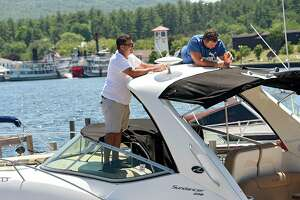 Eric LaPoint of Clifton Park, left, helps Anthony Grande of Waterford install a new night safety light on a boat on Lake George on Wednesday, June 17, 2020 in Lake Geroge, N.Y. The Million Dollar Beach will be open from 10 a.m. to 6 p.m. starting this weekend. (Lori Van Buren/Times Union)