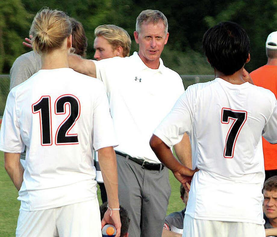 Edwardsville coach Mark Heiderscheid gives his team halftime instructions during a game last season at Alton High School.
