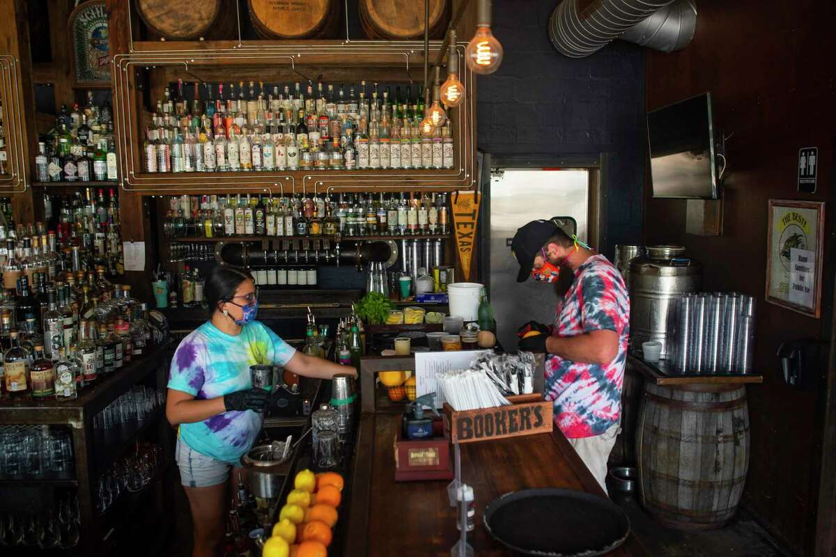 Bartender Melise Rodriguez (left) and server Josh Keating prepare drinks, Friday, May 22, 2020, at Eight Row Flint in Houston.