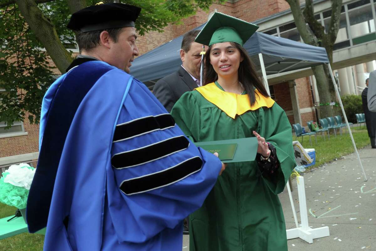 Valedictorian Karla Castro receives her diploma from Principal Joseph Raiola during graduation for the Bassick High School Class of 2020, in Bridgeport, Conn. June 18, 2020. There was confetti, signs, horn honks, and cheers as students popped out of the car at various stages for an Instagram shot, a diploma presentation, a professional photo in front of the school's stone columns and finally a station to pick up their the tassel and a congratulatory box of chocolates. What the event lacked in handshakes and hugs it made up for in smiles.