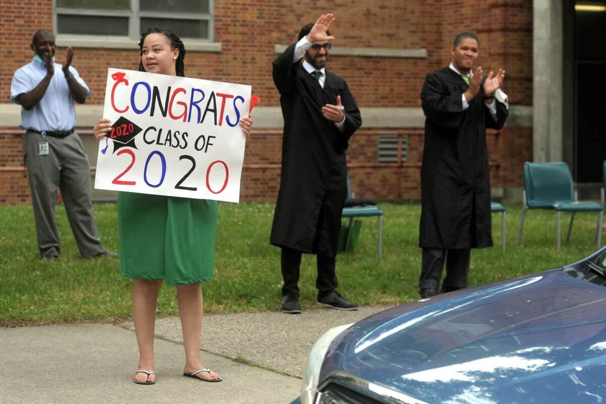 Faculty and staff cheer for graduates during graduation for the Bassick High School Class of 2020, in Bridgeport, Conn. June 18, 2020. Instead of sitting on stage, school board members - at Bassick, Bobbi Brown, Albert Benejan, Joseph Sokolovic and John Weldon attended - served as part of the cheering squad. Weldon, the board chair, also served at times as doorman, opening the car door for graduates as the emerged to get their diploma. Later, he called Bassick's 85th annual graduation ceremony awesome and truly unique.