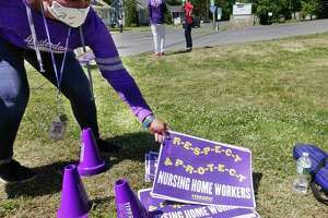 Ruthie Young with SEIU 1199 Healthcare East picks up signs to hand out to workers from the Diamond Hill nursing home during a rally outside the home on Thursday, June 18, 20202, in Schaghticoke, N.Y. Workers at the home, who are without a contract, say that they have  concerns over the homeÕs operations during the pandemic. (Paul Buckowski/Times Union)