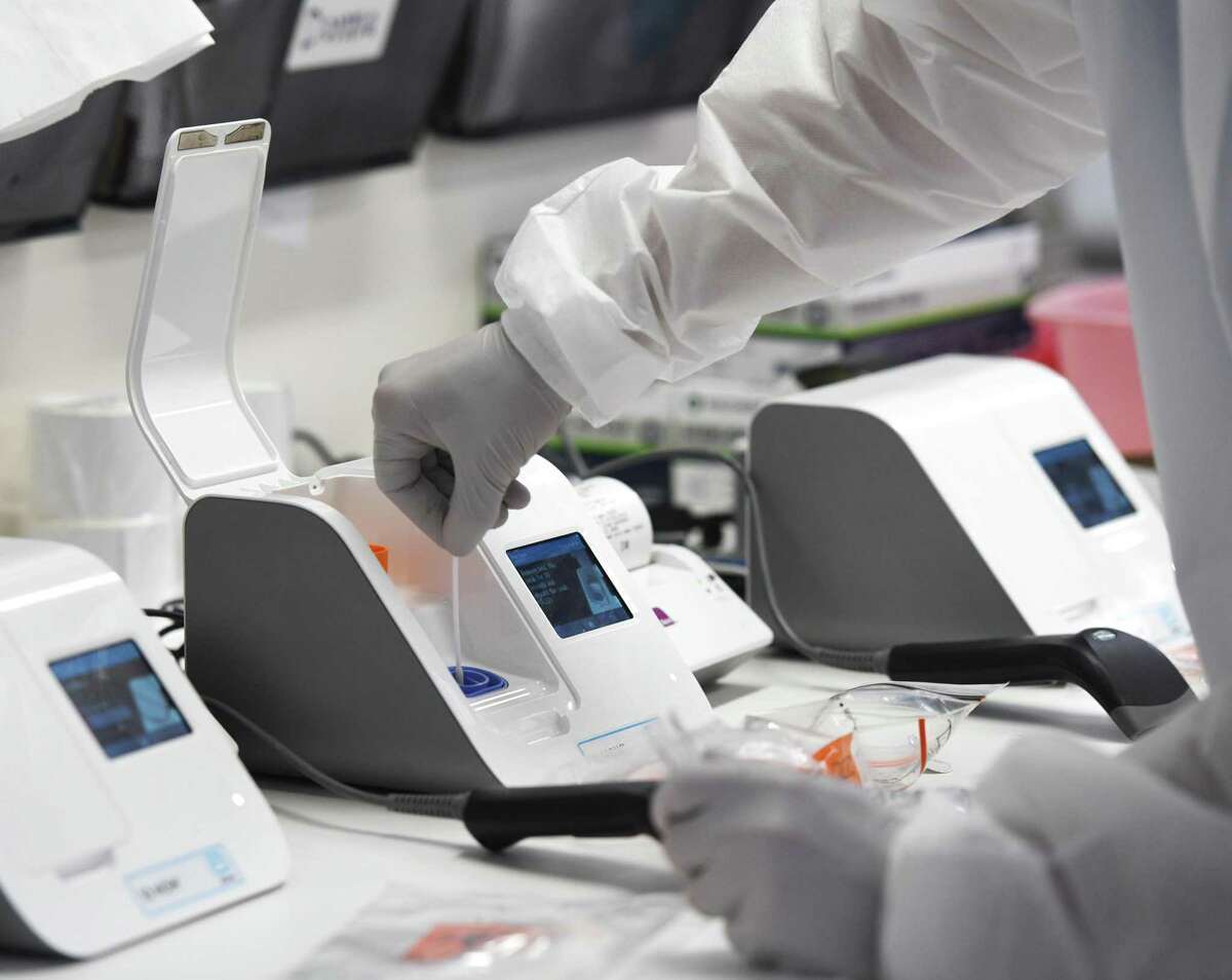 A medical laboratory scientist inserted a patient's swab sample into the coronavirus testing machine in the lab at Stamford Hospital, in a May file photo.