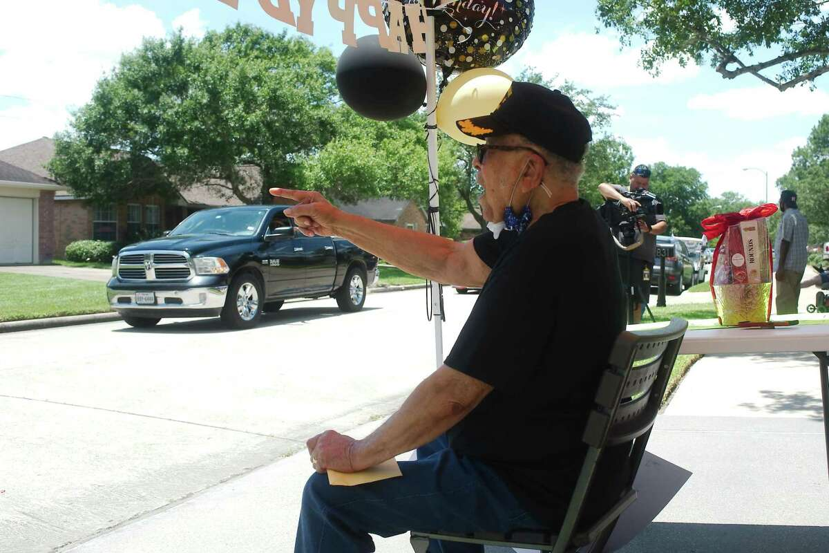 Pearland resident Charles Mills speaks to friends as they parade past his home and offer birthday wishes in honor of his 100th birthday.