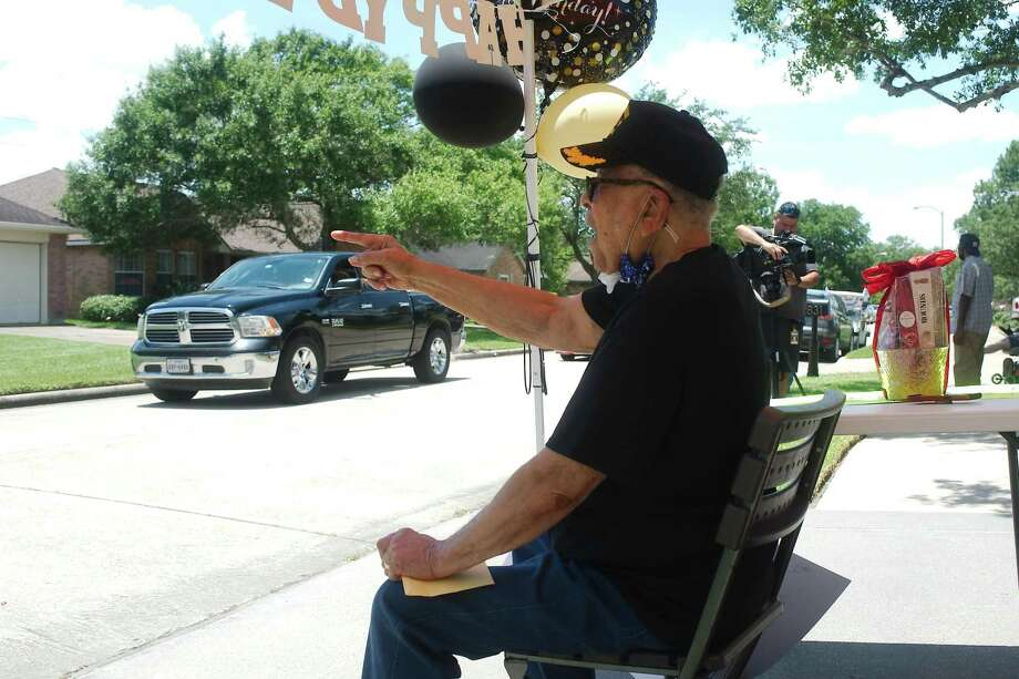 Pearland resident Charles Mills speaks to friends as they parade past his home and offer birthday wishes in honor of his 100th birthday. Photo: Kirk Sides / Staff Photographer / © 2020 Kirk Sides / Houston Chronicle