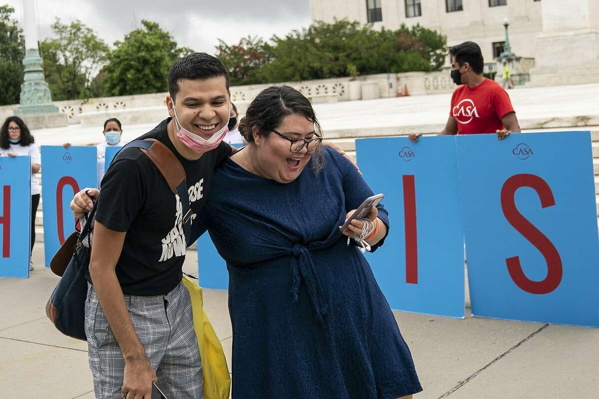 WASHINGTON, DC - JUNE 18: Greisa Martinez (R), who grew up as an undocumented immigrant in Dallas, Texas, reacts and she reads the Supreme Court's decision regarding the Trump administration's attempt to end DACA outside the U.S. Supreme Court on June 18, 2020 in Washington, DC. On Thursday morning, the Supreme Court, in a 5-4 decision, denied the Trump administration's attempt to end DACA, the Deferred Action for Childhood Arrivals program. (Photo by Drew Angerer/Getty Images)
