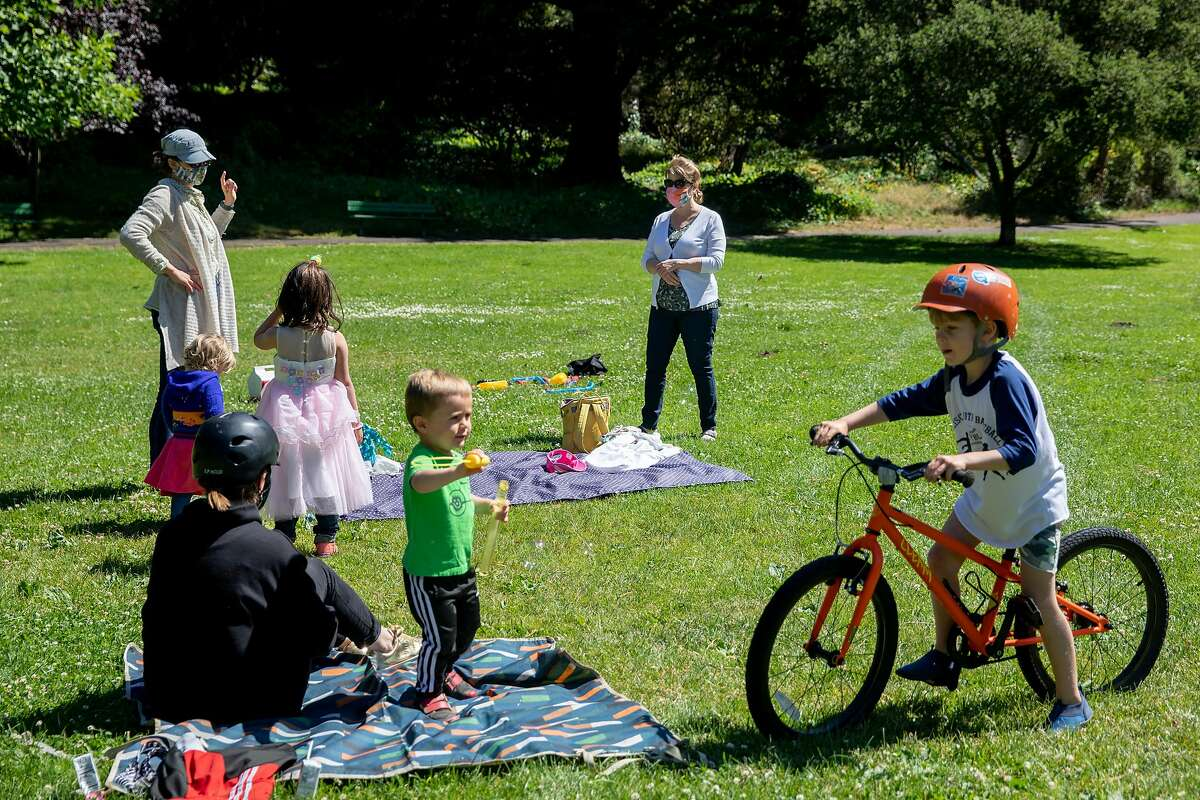 """Friends and family socially distance as they gather to celebrate Addie McLaughlin's 6th birthday at Golden Gate Park in San Francisco, Calif. Saturday, June 13, 2020. Shelter-in-place rules in various counties across the Bay Area have began to ease up, giving residents more flexibility with their outdoor activities such as having """"social bubbles"""" of no more than twelve others."""