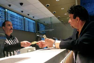 FILE - In this Jan. 29, 2020, file photo, a gambler makes bets on the upcoming Super Bowl at Bally's casino in Atlantic City N.J. The coronavirus pandemic could lead to a quicker expansion of sports betting and internet gambling in the U.S. as states deal with huge budget deficits and look for new tax revenue wherever they can find it.