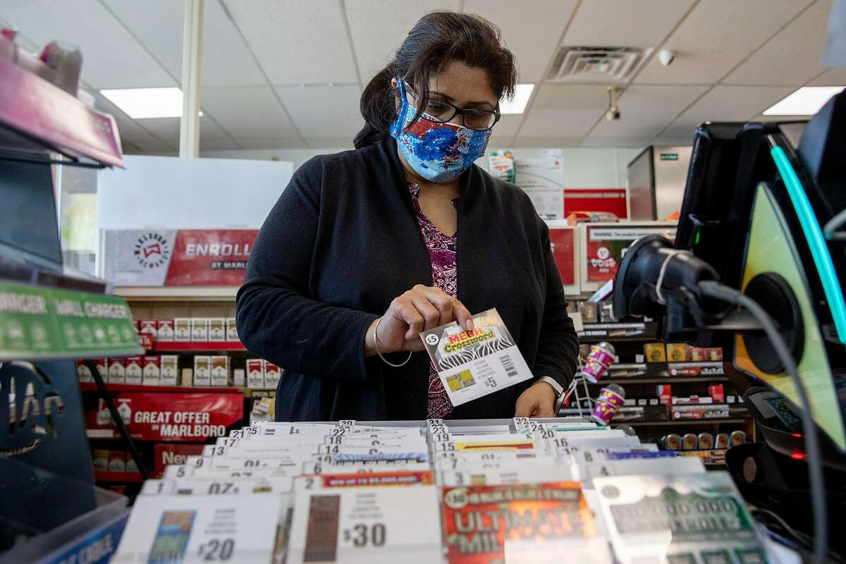 Renu Sikand works to update her inventory of scratcher tickets already in scarce supply behind the counter at 7-Eleven in Albany, Calif. Tuesday, June 16, 2020. A serious shortage of California Lottery scratchers in the Bay Area, and possibly the state, over the last two weeks has left some stores such as 7-Eleven, Safeway and other markets empty-handed as deliveries they were promised never arrived.