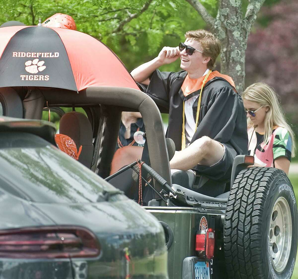 2020 Ridgefield High School graduate John Briody watches the ceremony on the big screen from his Jeep. Thursday, June 18, 2020.