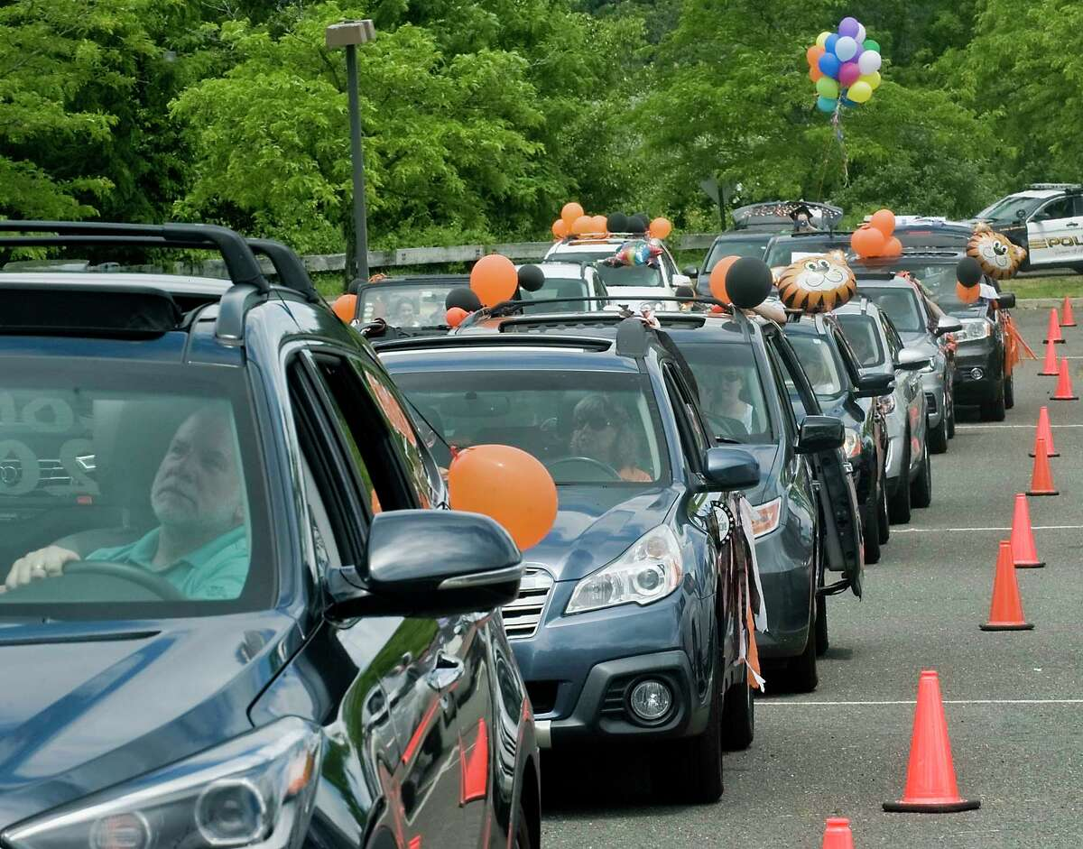 Cars lined up to watch the Ridgefield High School graduation ceremony on the big screen in the school parking lot. Thursday, June 18, 2020. Applause, cheers and the honking of horns followed speeches, and punctuated the reading of graduates' names.