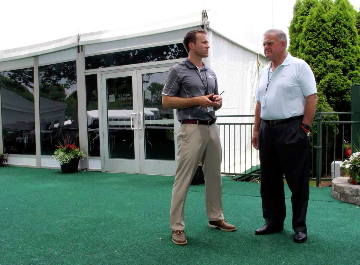 Nathan Grube, left, the director of the Travelers Championship golf tournament, and Andy Bessette, executive vice president of Travelers, chat at the ALS Center of Excellence at the TPC River Highlands course in Cromwell, Conn., on Monday, June 19, 2017. The center is designed to let patients with ALS attend the PGA Tour event. (AP Photo/Pat Eaton-Robb)