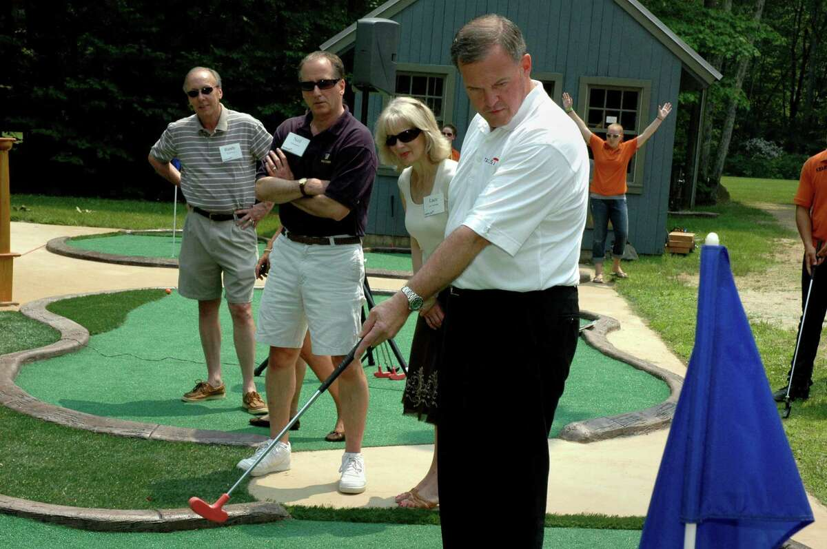 Andy Bessette, executive vice president and chief administrative officer at Travelers Insurance Company, follows his putt on the new handicap-accessible mini golf course at the Hole in the Wall Gang Camp in Ashford, Conn., during a ribbon-cutting event on Saturday, June 14, 2008. The future of the camp founded by actor Paul Newman to benefit critically ill children will be unaffected by the actor's health, the camp's executive director said Saturday. The Hole in the Wall Gang Camp, named for the group of outlaws made famous by Newman's popular 1969 movie,